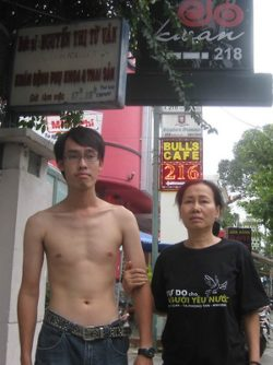 Police detained Nguyen Tri Dung and his mother to prevent them from attending the trial of three prominent bloggers, including his father Nguyen Van Hai on September 24, 2012. After the court sentenced the bloggers, police stripped Dungs t-shirt which featured the slogan: Freedom for Patriots. © 2012 VRNs