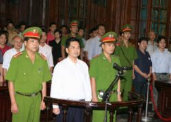 Cu Huy Ha Vu stands between policemen in the dock during his trial at a court in Hanoi