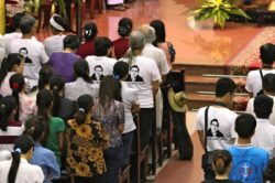 Supporters wear t-shirts bearing a portrait of Le Quoc Quan during a mass held for him at a Catholic church in Hanoi on July 7, 2013. (Photo: AFP)