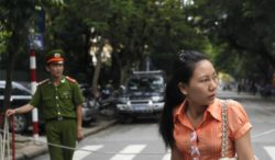 A plainclothes and a uniformed police officer stand in front of a court in Hanoi. Reuters