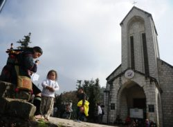 A Hmong woman sells souvenirs in front of a church in Sapa in Vietnams northern highlands.  AFP PHOTO