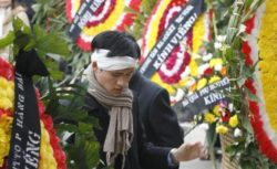 Nguyen Tien Trung stands between wreaths during a funeral for Hoang Minh Chinh in Hanoi