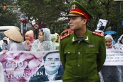 A policeman stands in front of supporters of lawyer Le Quoc Quan, as they hold a banner of him outside a court in Hanoi, 18 February 2014