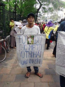 Mr. Tuyen with banner demanding for his mother release at a demonstration in Hanoi