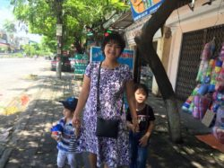 Ms. Nga and her two sons Tai and Phu near her rent house in Phu Ly