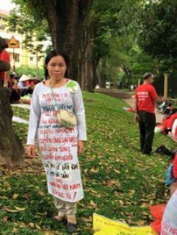 Widow Vu Thi Hai with special clothes to protest land seizure in Hanoi street