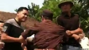 Two plainclothes policemen attack human rights activist Truong Van Dung (center) on Oct. 16