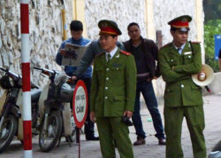 Police in uniforms and plainclothes patrol the area outside the courthouse in Hanoi, April 4, 2011.