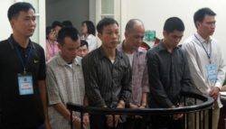 Defendant Nguyen Duc Toan (second from right) and other attackers at a trial on Nov. 16