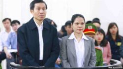 Vietnamese political blogger Nguyen Huu Vinh (L) and his assistant Nguyen Thi Minh Thuy stand at the dock during their trial in Hanoi on March 23, 2016.  © 2016 Reuters