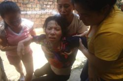 Tran Thi Hong is helped by friends after a tortuous encounter with Vietnamese authorities.