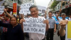 Political dissident Nguyen Quang A (C) holds a sign which reads