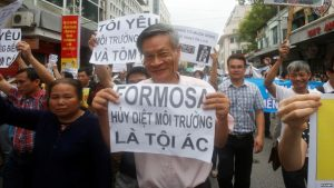 """Political dissident Nguyen Quang A (C) holds a sign which reads """"Formasa - damaged the environment and is a criminal"""" during a protest in Hanoi, Vietnam, May 1, 2016."""